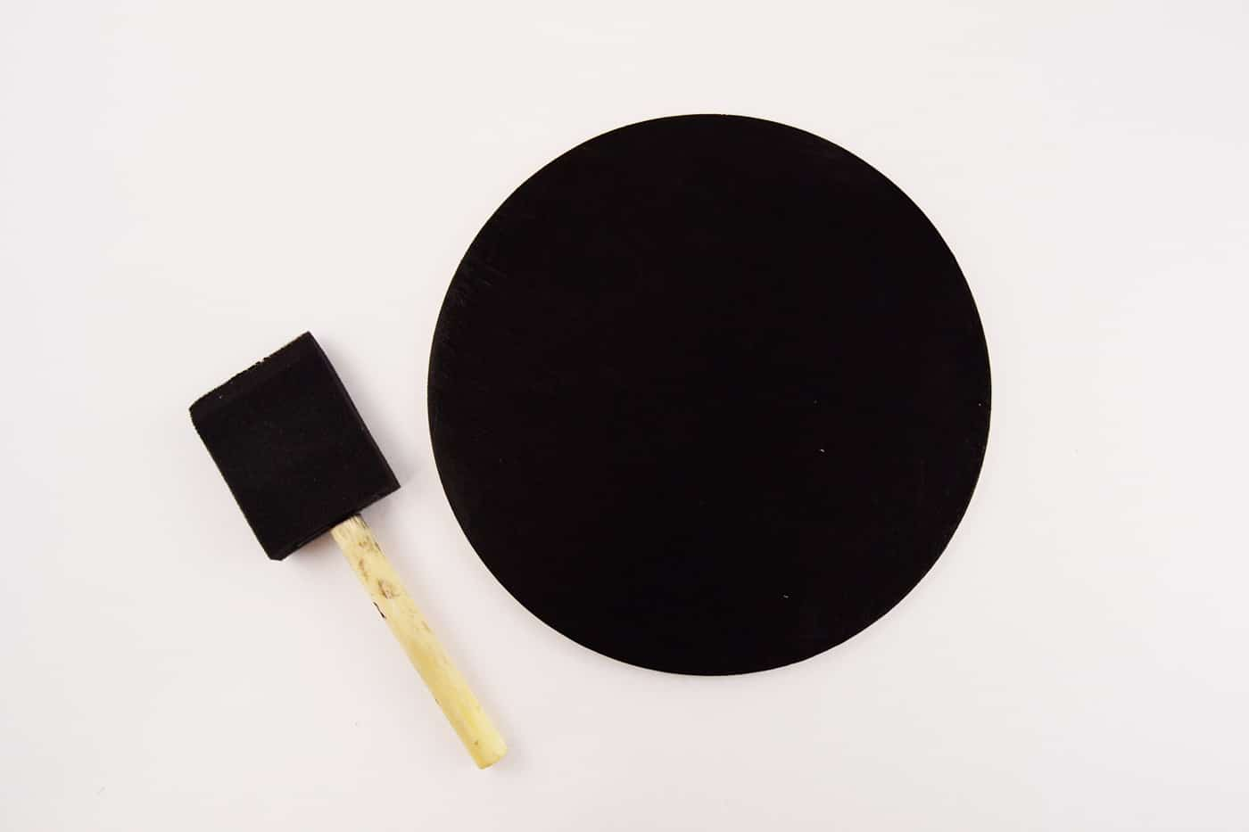 Wood circle painted black with a foam brush laying next to it
