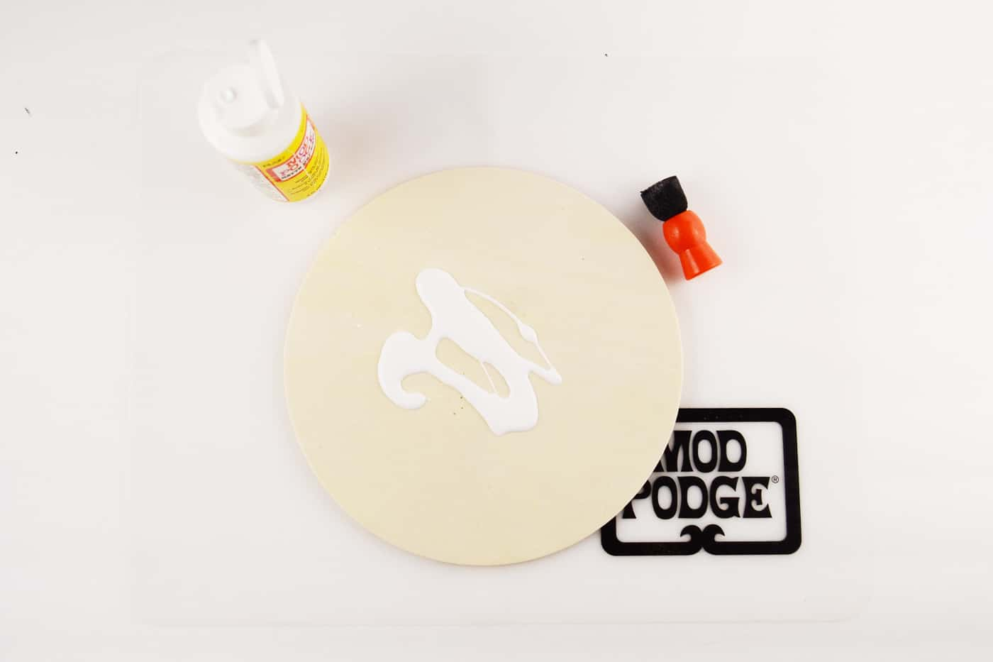 Mod Podge Matte on top of a wood circle with a spouncer next to it