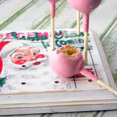 Learn how to make this DIY cake pop stand from a wood plaque, vintage Christmas graphics, and Mod Podge. It's really easy and the perfect party display!