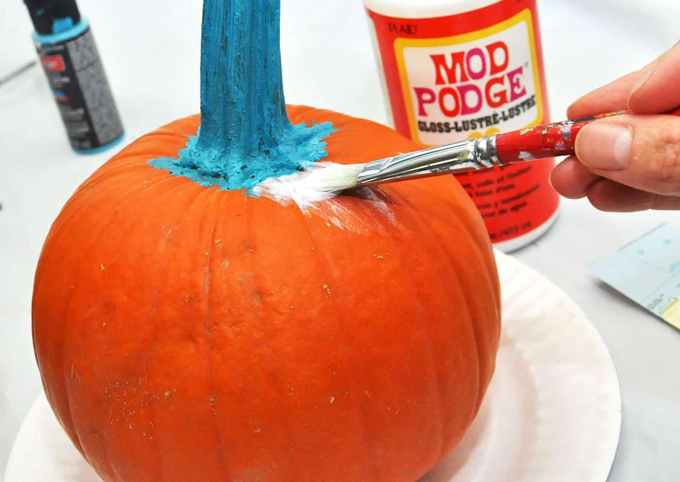 Applying Mod Podge to a pumpkin