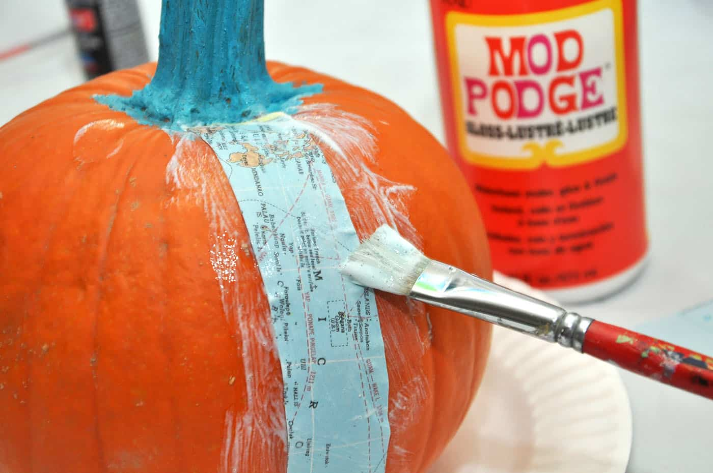 Applying a piece of map to a pumpkin