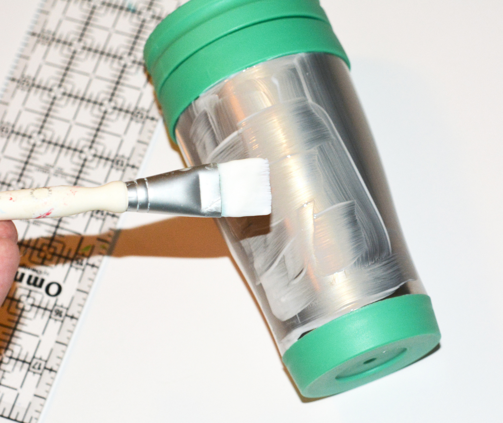 Painting Mod Podge Dishwasher Safe onto the side of a travel mug with a paintbrush