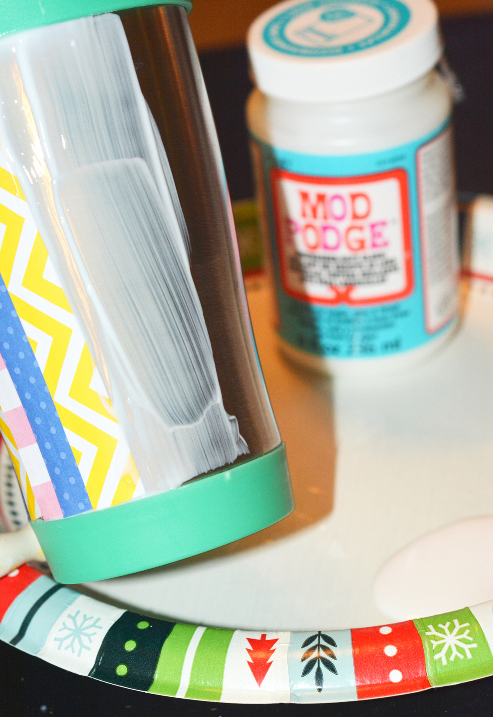Placing paper on top of the Mod Podge on the side of the mug