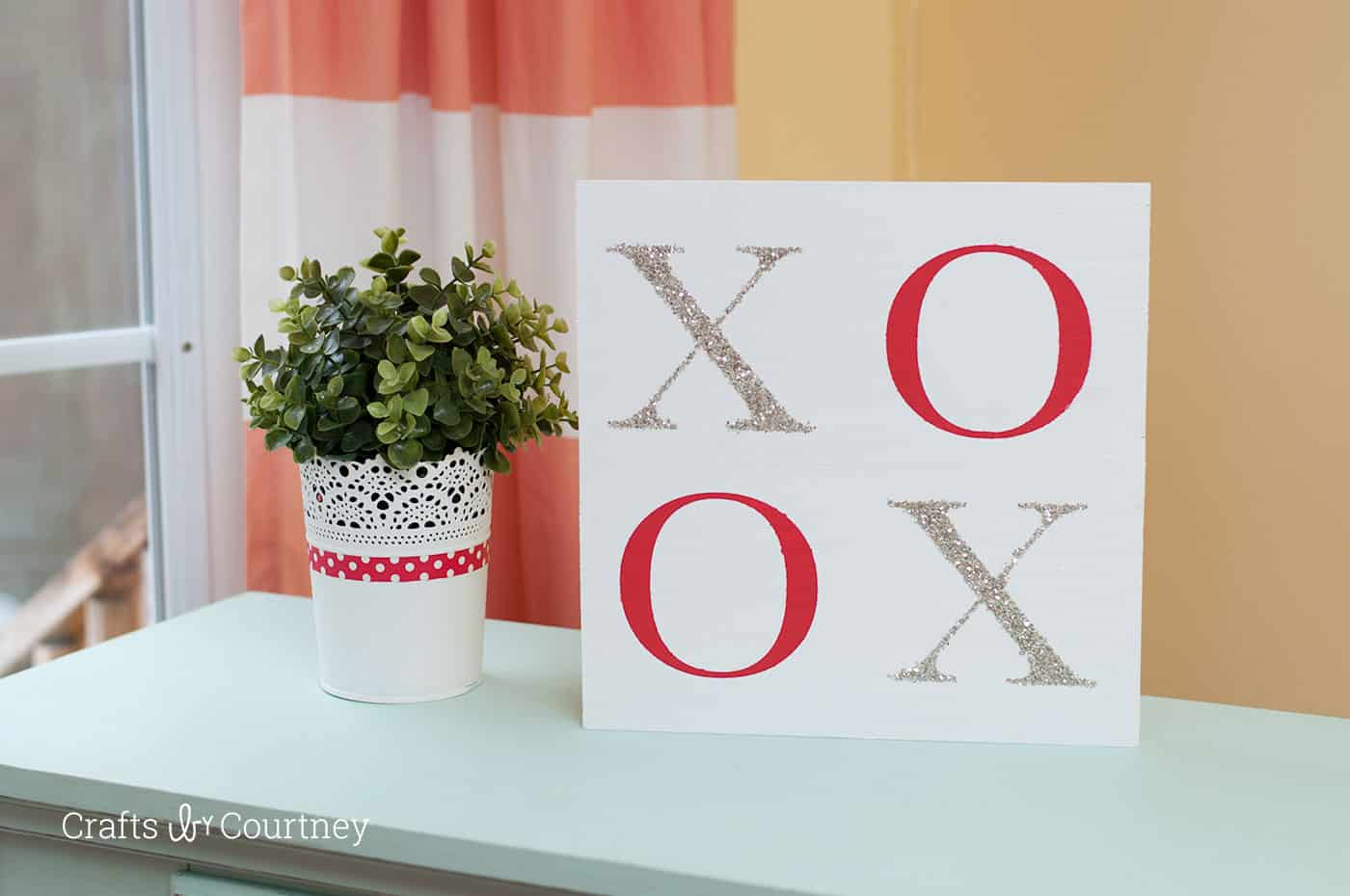 Use Mod Podge and glitter to make this sparkly Valentine's Day sign - an XOXO sign that will look great displayed on a table or mantel! This is REALLY easy to make.
