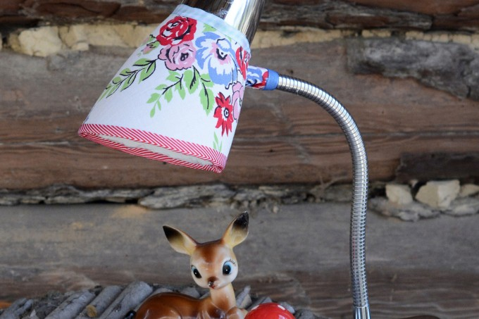 Give an old, beloved clip lamp a facelift with fabric and Mod Podge! It's a very easy and budget friendly project - and you'll love the results!