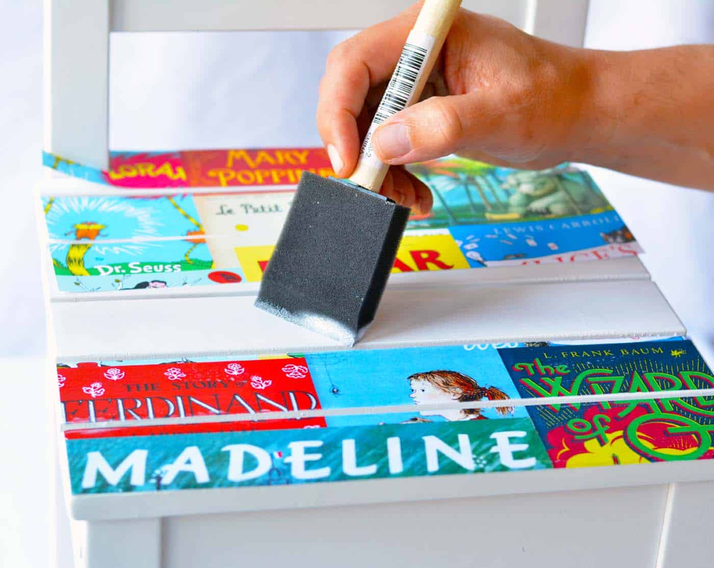 Applying book cover images to the top of a chair with Mod Podge and a foam brush
