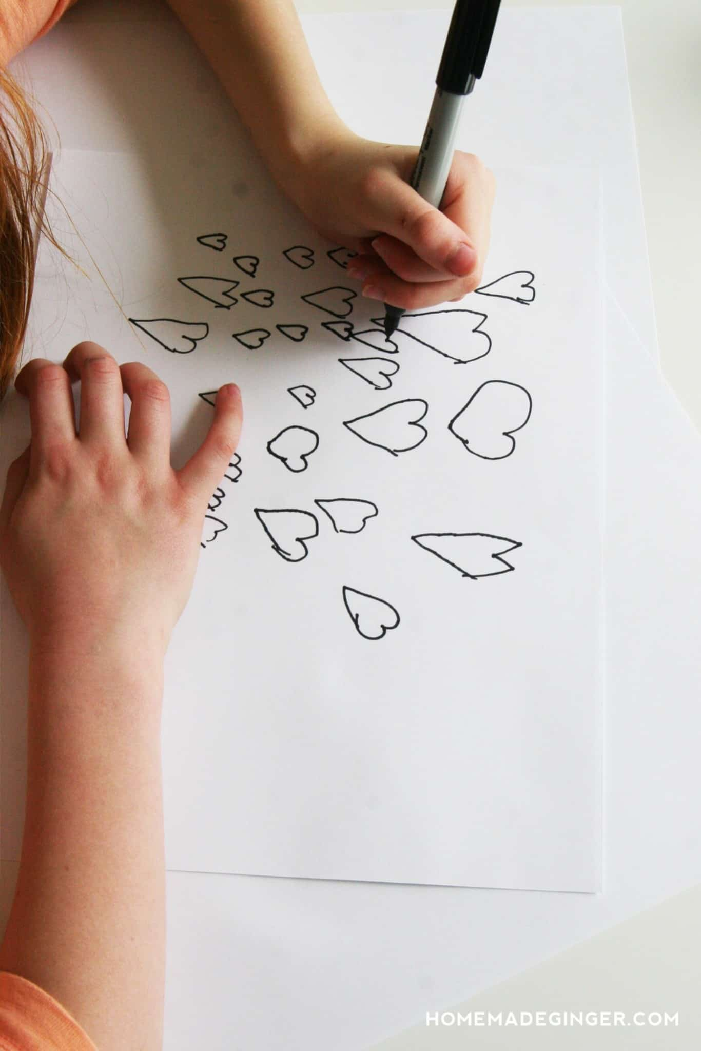 Child drawing hearts on a piece of white paper with a Sharpie