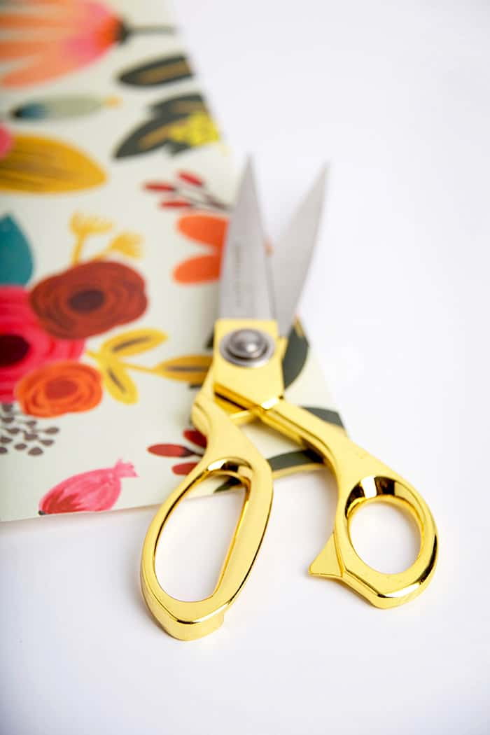 Cutting out paper with gold handled scissors