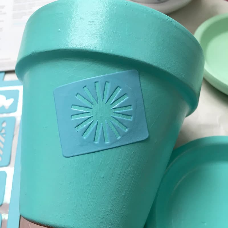 Applying an adhesive stencil to a clay pot