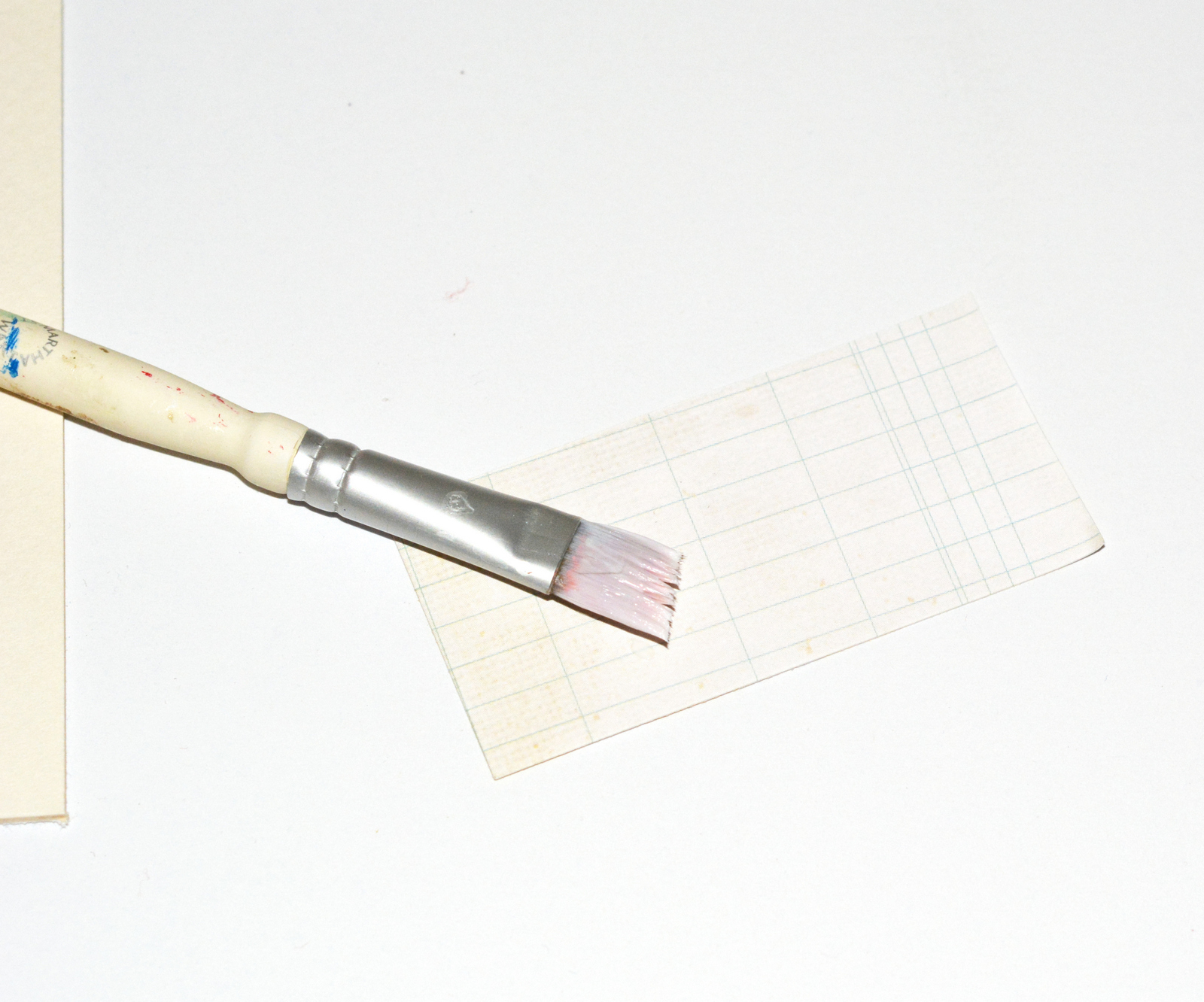 Brushing Mod Podge on the back of a piece of paper with a paintbrush