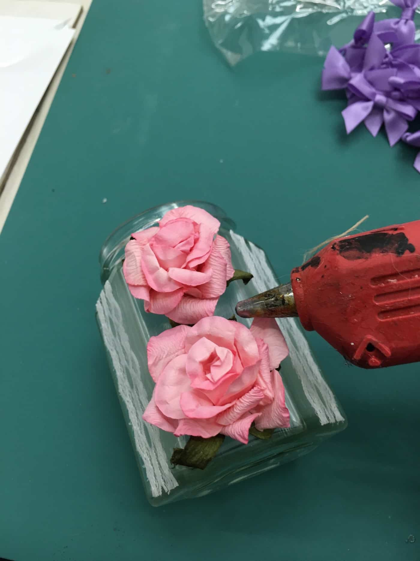 Applying roses to a mason jar with hot glue