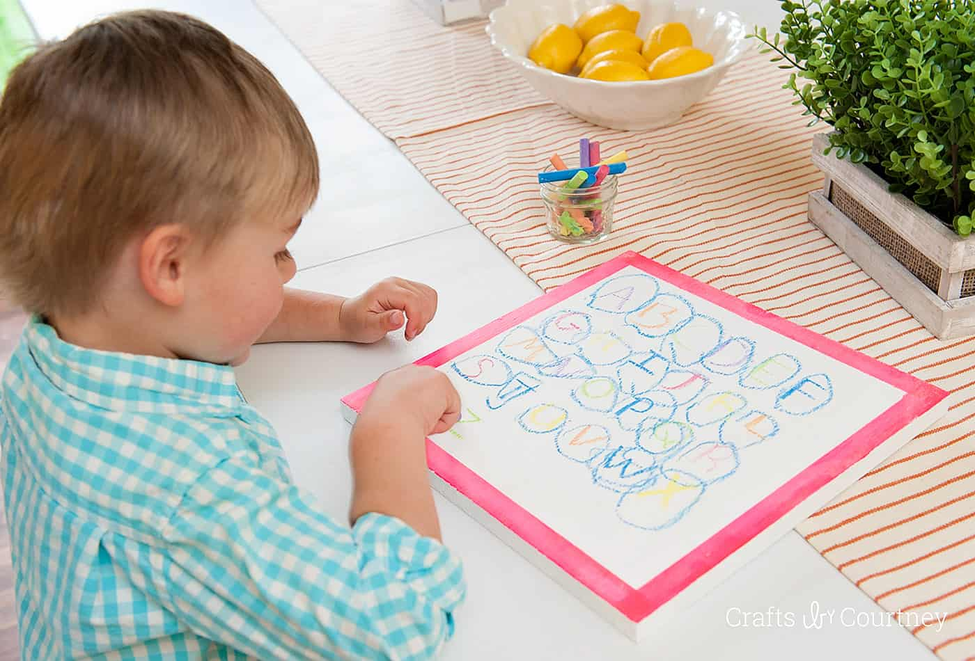 Child using colored chalk on top of a white chalkboard
