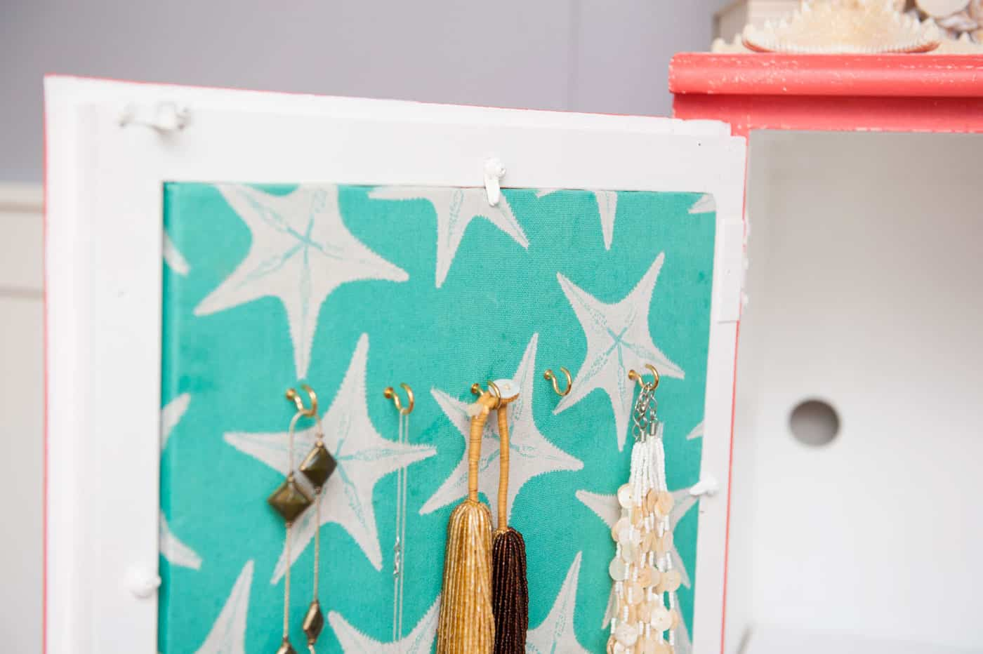 Courtney revamped her bathroom cabinet with pretty paint colors - and turned the inside into a cork board jewelry organizer with Mod Podge and fabric!