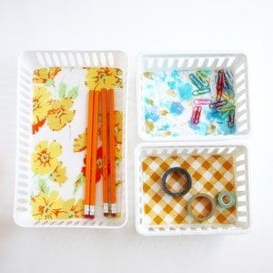 Gussy up some organizer bins with Mod Podge in this easy dollar store craft! This is great for using up those small pieces of fabric for something pretty.