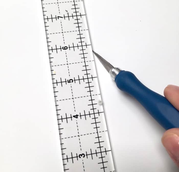 Craft knife cutting paper next to a ruler