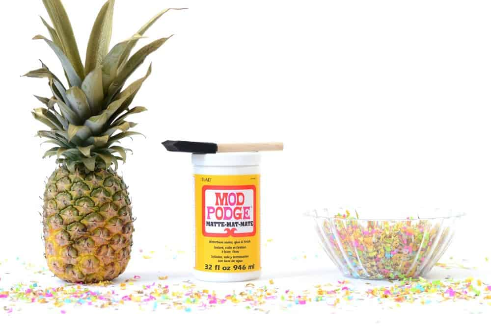 Pineapple, Mod Podge, foam brush, clear glass container of confetti