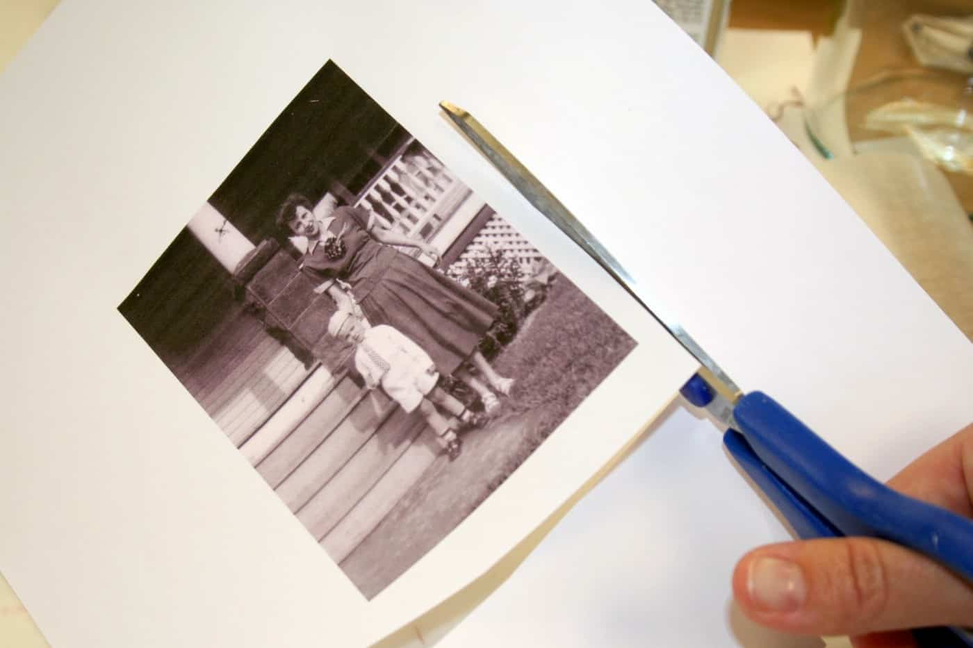 Cutting out a vintage image with blue handled scissors