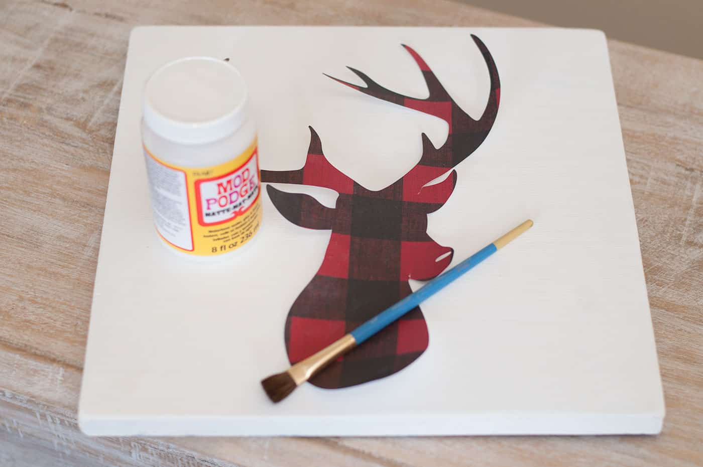 White wood piece, plaid deer head cut out of scrapbook paper, Mod Podge Matte, and a paintbrush