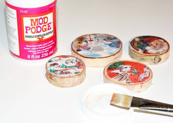 Bottle of Mod Podge sparkle, Christmas magnets on wood slices, and a paintbrush