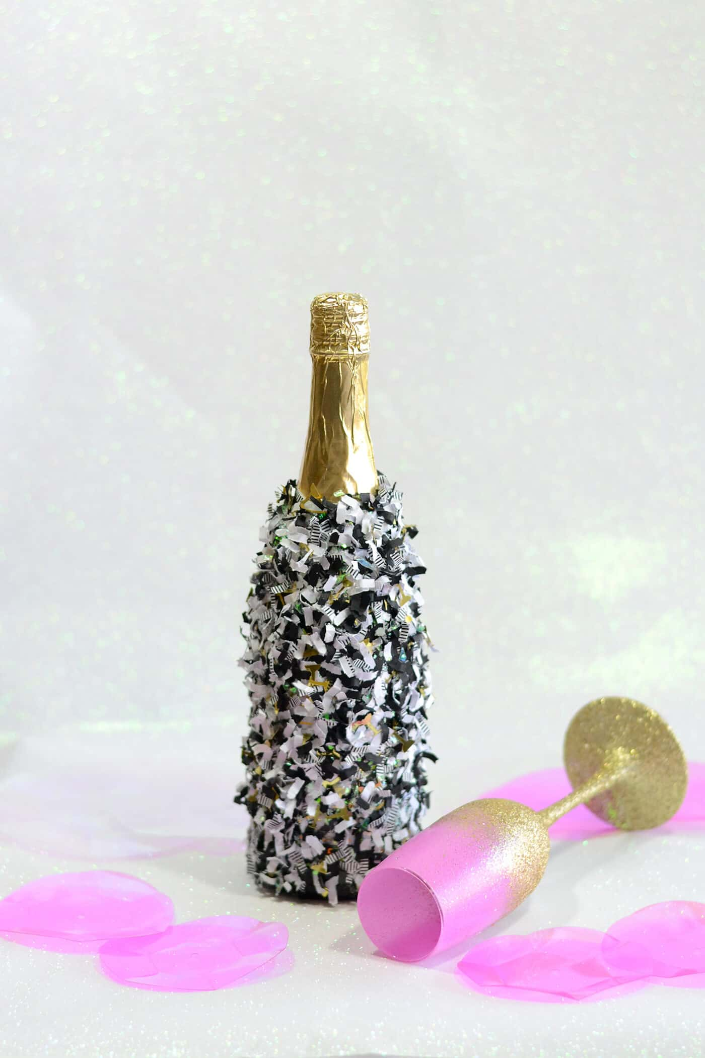 Use your favorite party confetti and Mod Podge to customize a champagne bottle for New Years Eve! Great for weddings too, or any other celebration.