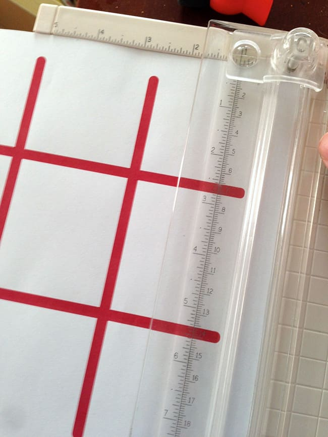 Trimming a tic tac toe game template with a paper cutter