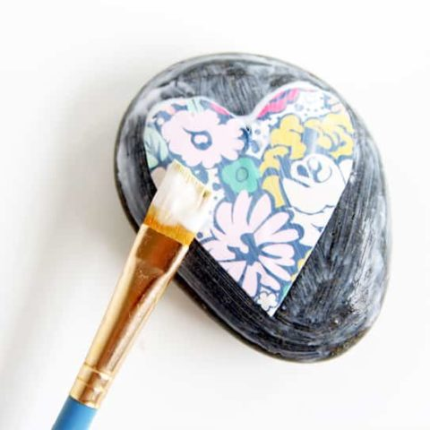 Make some pretty stones for your garden or desktop with a little bit of decoupage. It's easy to Mod Podge on rocks and the results are so pretty!