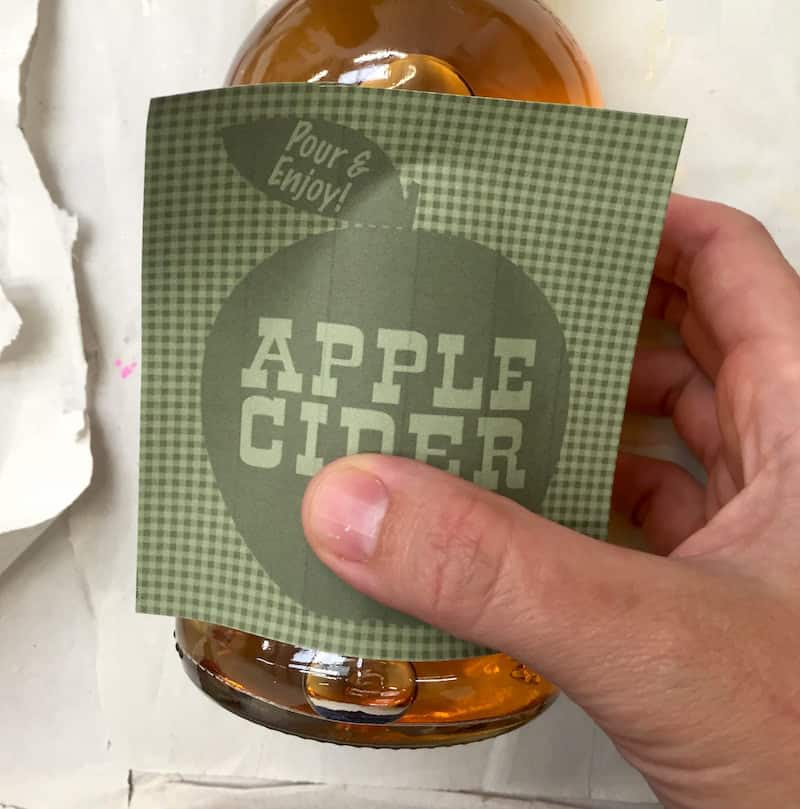 Placing an apple cider label on a bottle