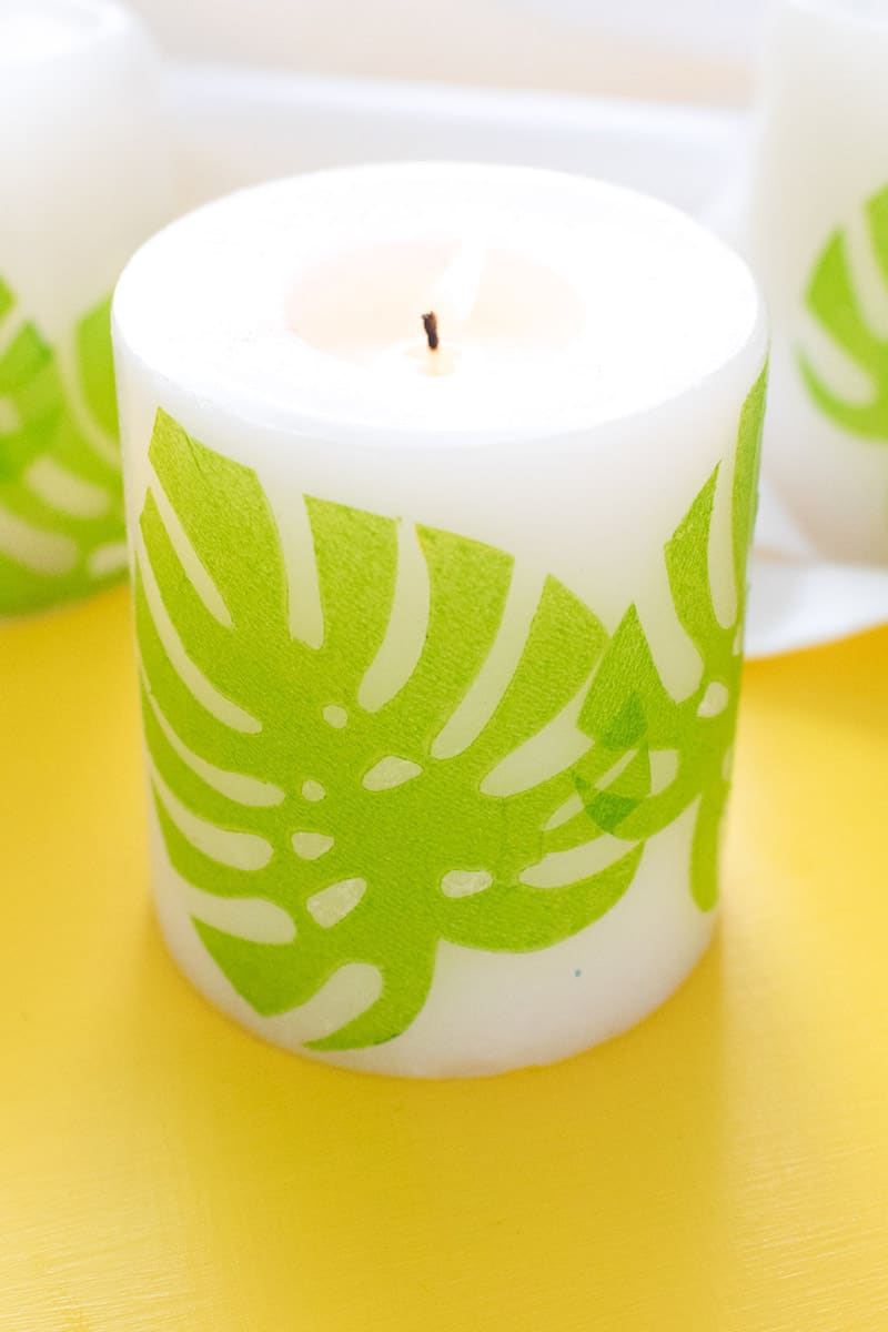 Use dollar store supplies to make these pretty decoupage candles! We added a tropical flair to ours, making them perfect for parties.