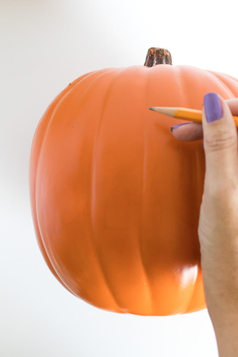 Drawing numbers on a faux pumpkin with a pencil