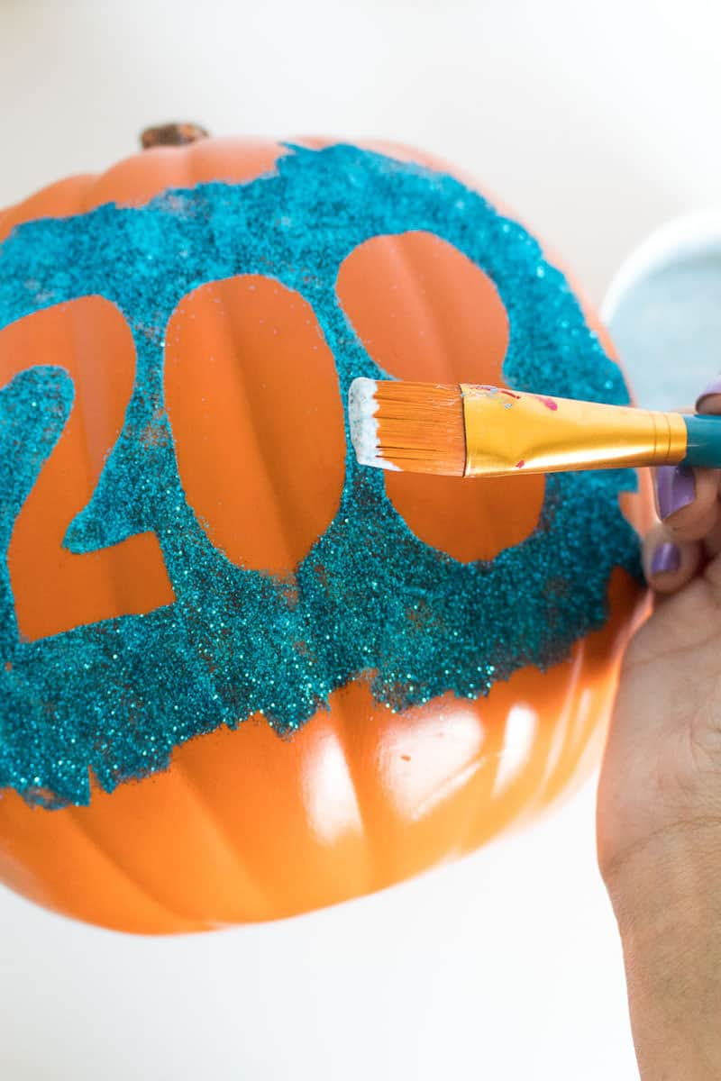 Adding Mod Podge Gloss to the top of a house number pumpkin