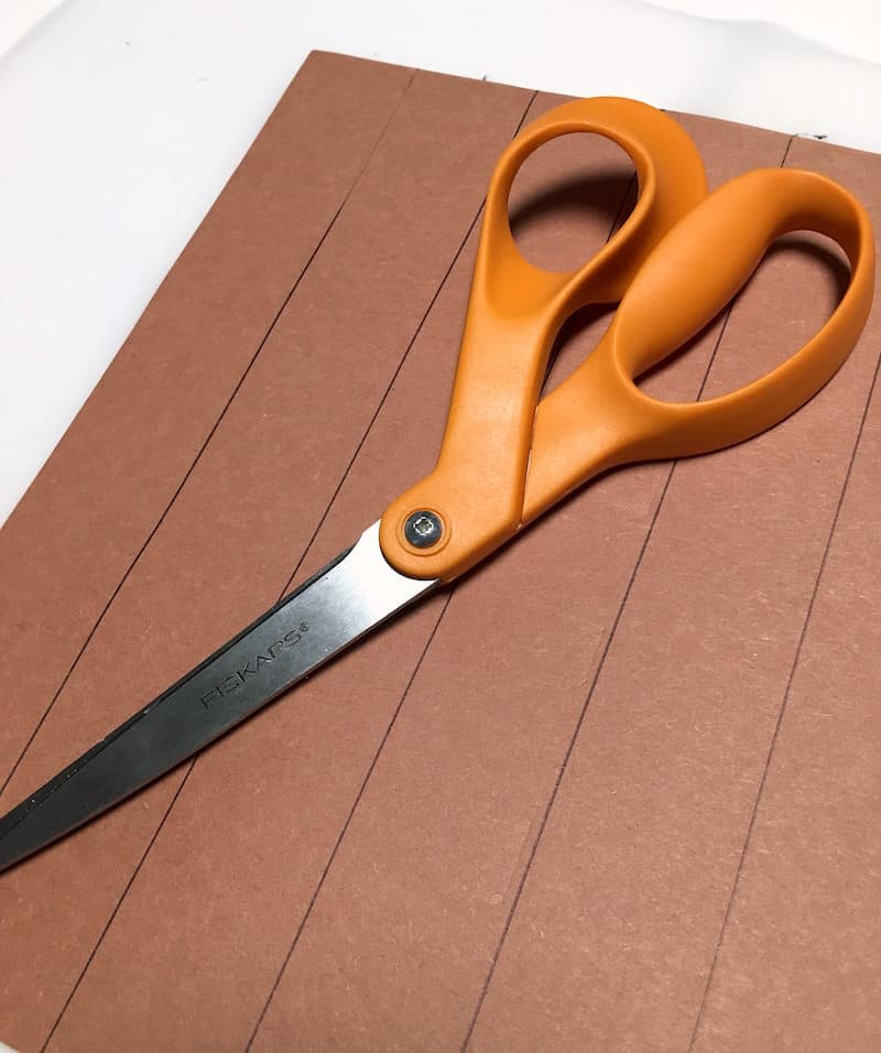 Brown construction paper with lines drawn on it and a pair of orange handled scissors
