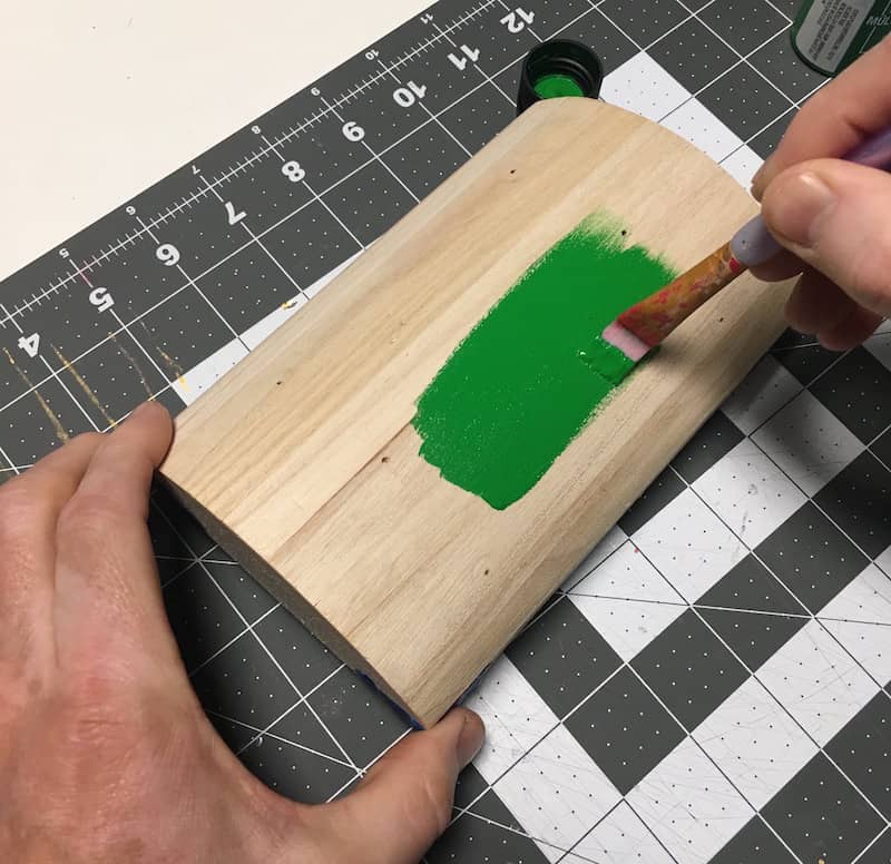 Paint a wooden treasure chest lid with green acrylic paint