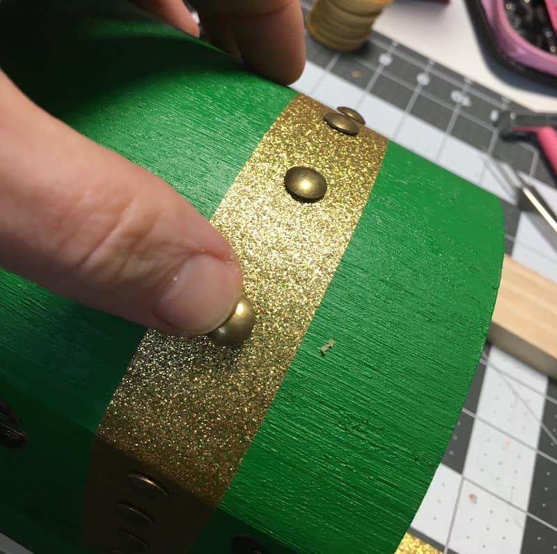 Place gold brads into a green painted wooden chest