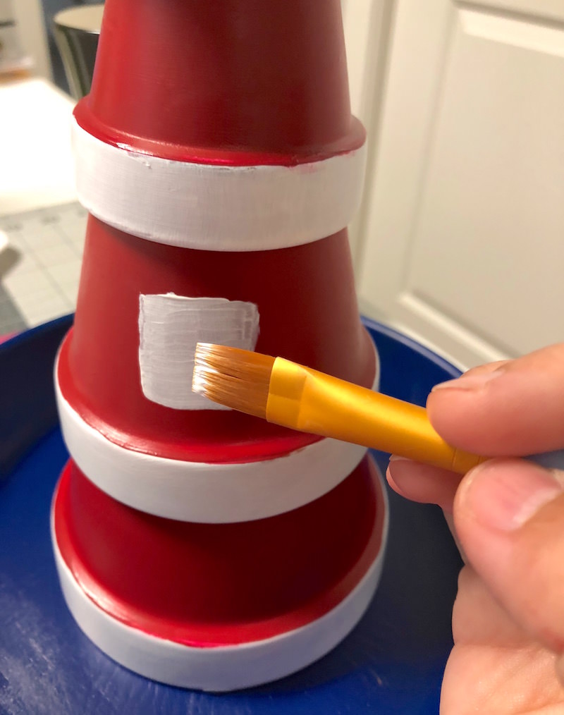 Paint the windows onto the DIY lighthouse bird feeder
