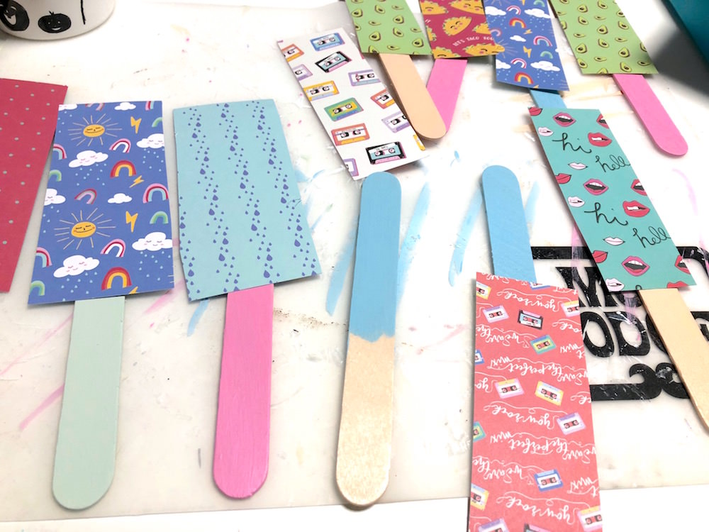 Scrapbook paper drying on popsicle sticks