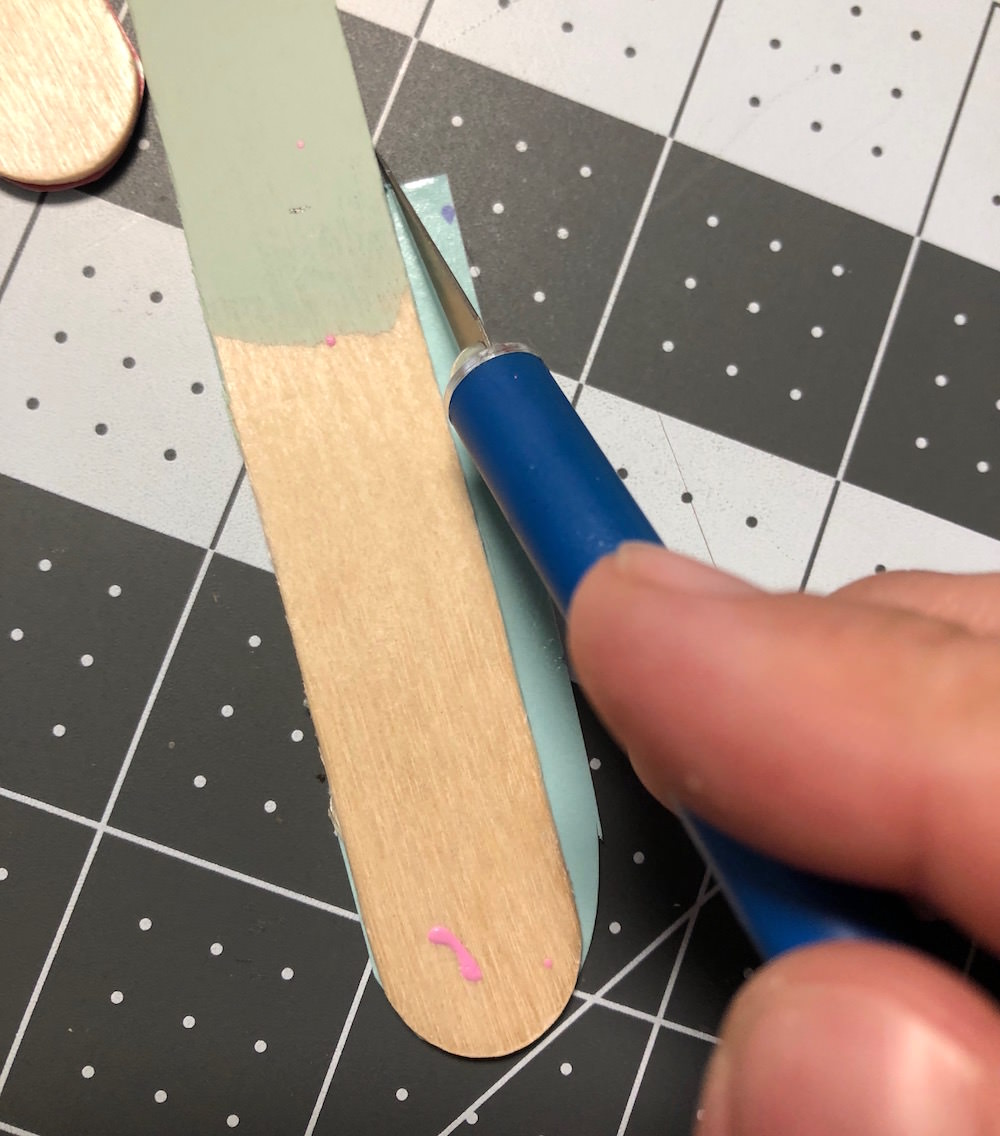 Trim popsicle stick with a craft knife