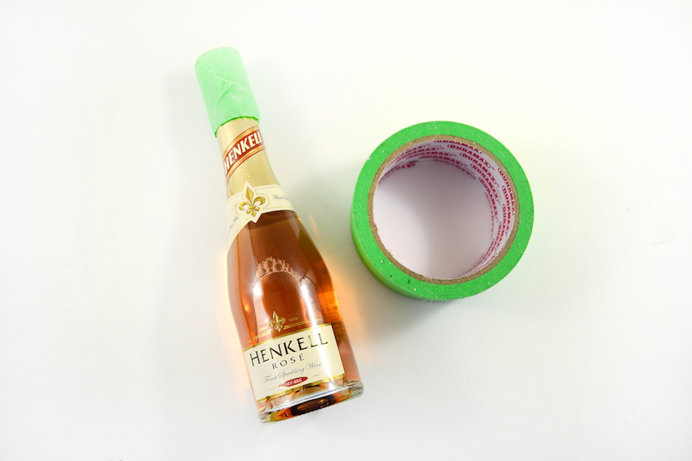 Tape up the top of your mini champagne bottle