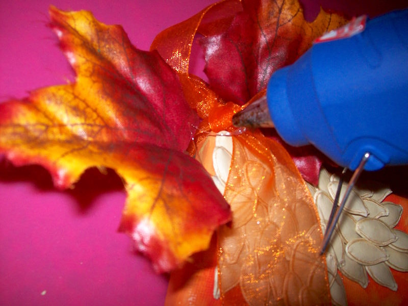 Add ribbon and faux leaves to canvas with a hot glue gun