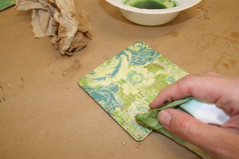 Add alcohol ink to the edges of a coaster with a paper towel