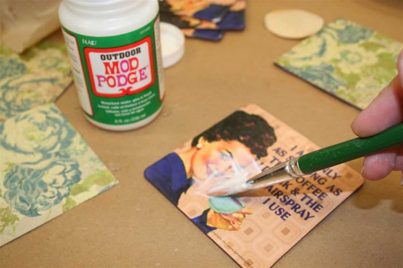 Paint Mod Podge Outdoor on the top of a dollar coaster with a paintbrush