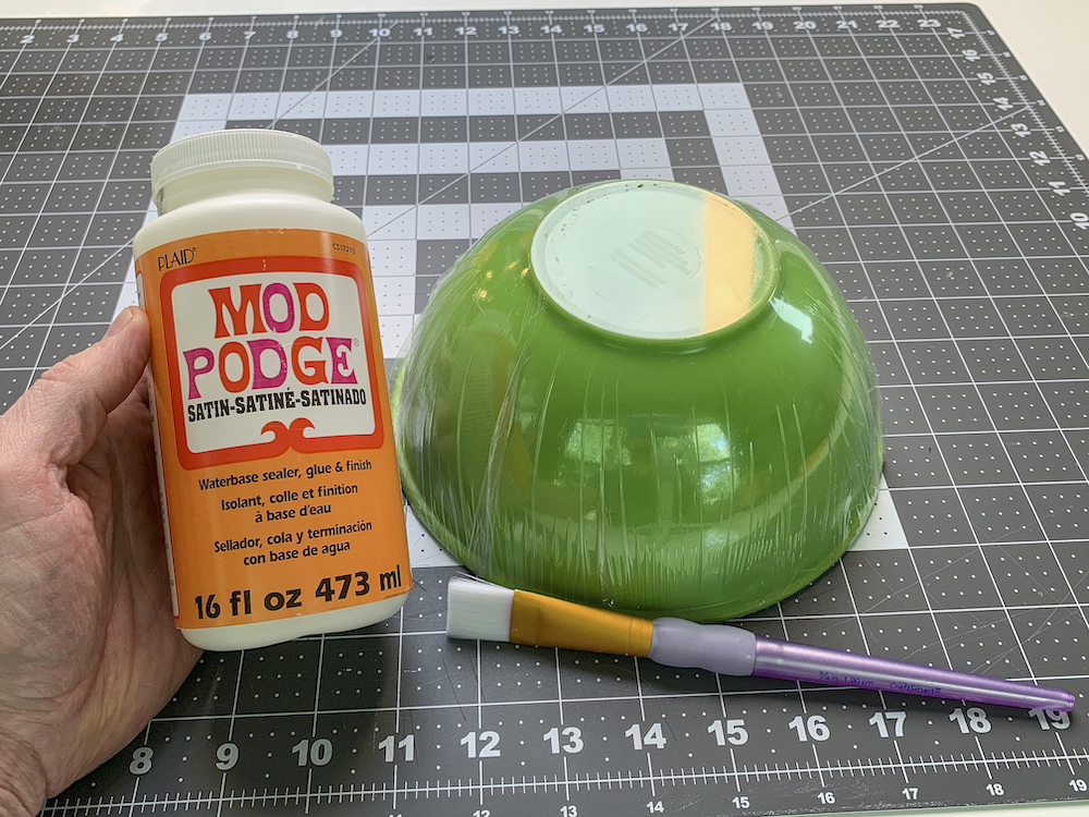 Bottle of Mod Podge Satin next to a bowl wrapped in plastic wrap with a paintbrush