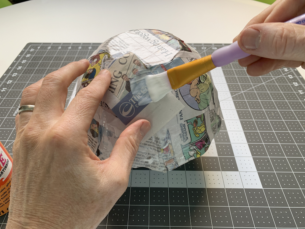 Layering newspaper on top of a paper mache bowl