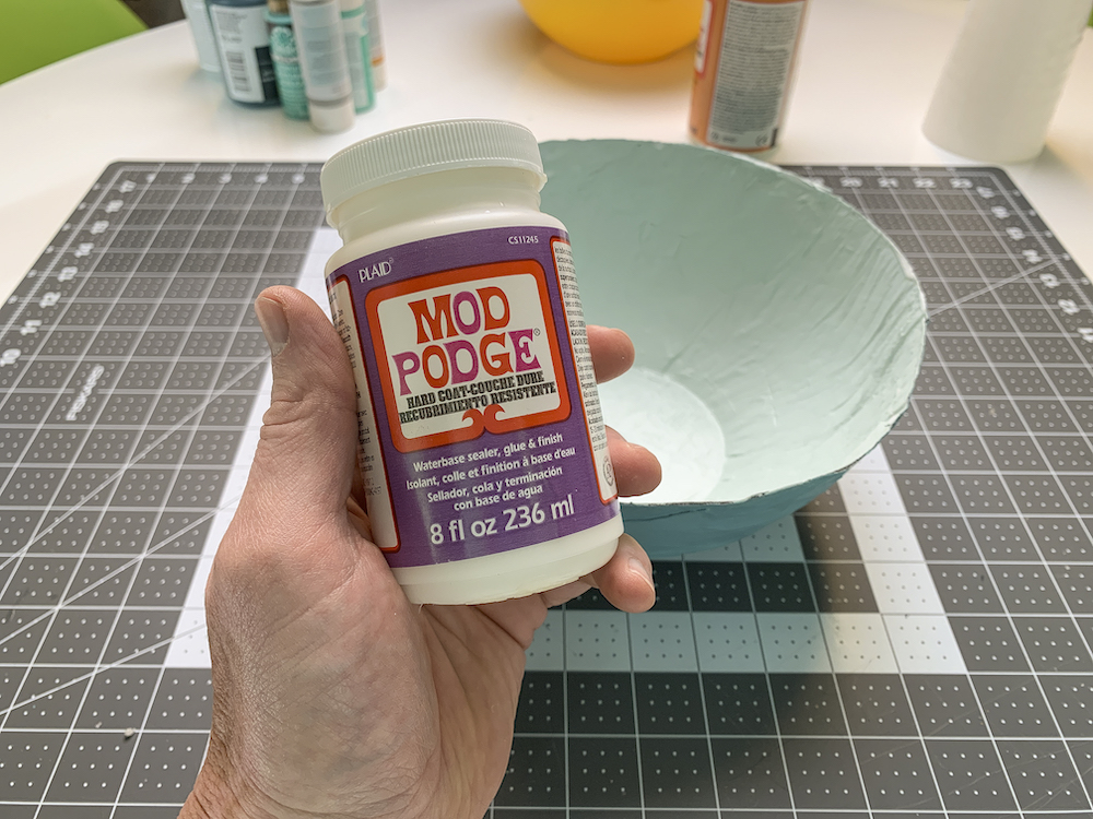 Mod Podge hard coat with a newspaper bowl in the background