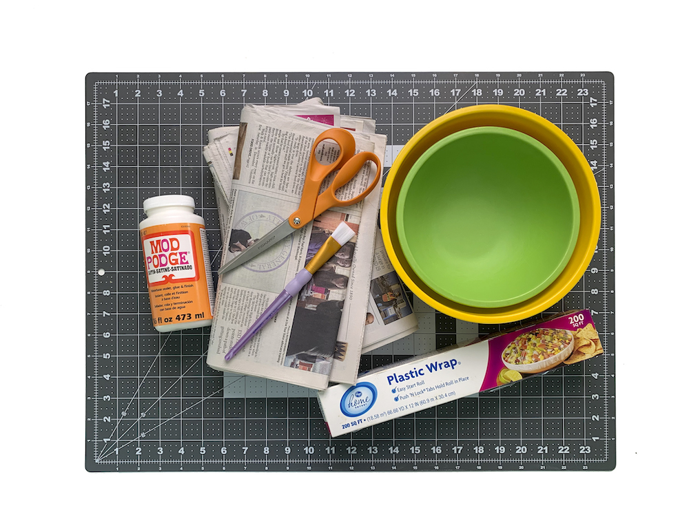 Mod Podge newspaper bowls plastic wrap and paintbrushes
