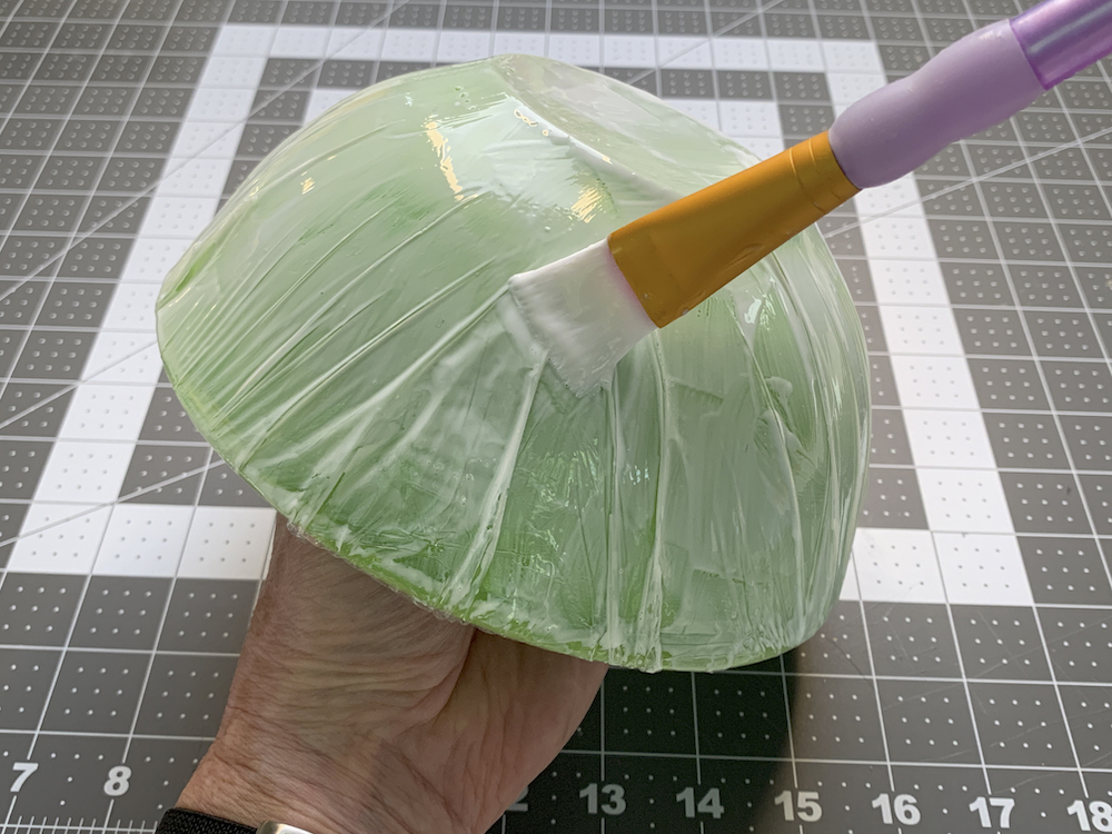 Painting Mod Podge on top of a bowl covered with plastic wrap