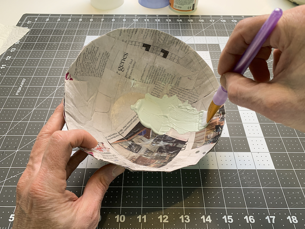 Painting a newspaper bowl with acrylic paint
