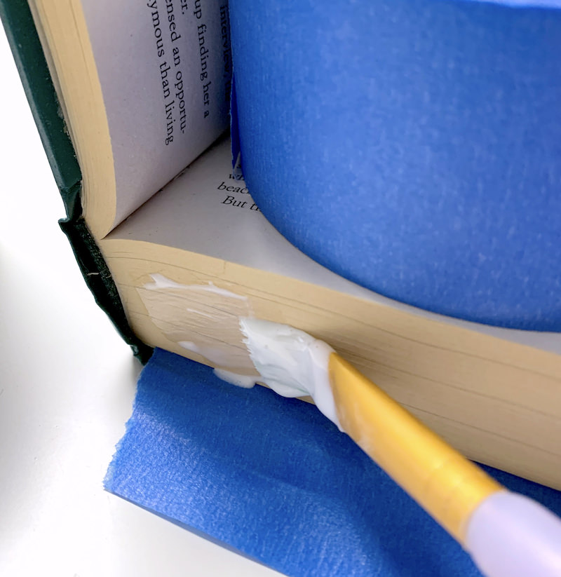 Applying Mod Podge to the edge of the book