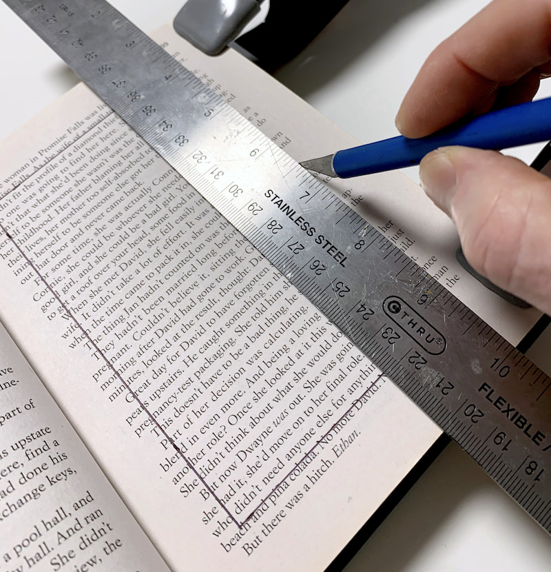 Using a ruler and craft knife to cut into the book pages