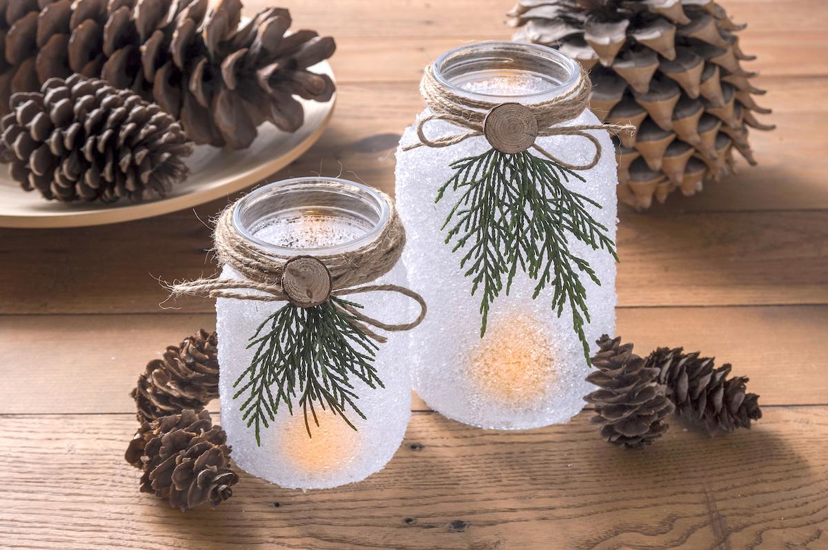Luminárias de natal em frasco de pedreiro iluminado na frente de pinhas