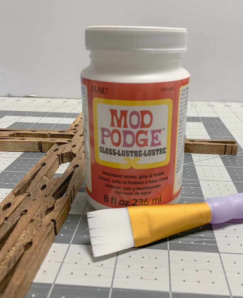 Bottle of Mod Podge next to a clothespin cross with a paintbrush